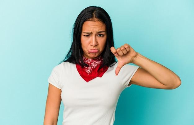 親指を下に、失望の概念を示す青い背景に分離された若いベネズエラの女性。