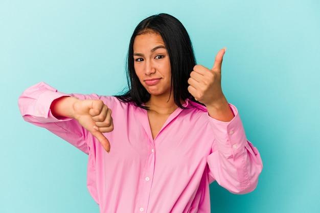 親指を上と親指を下に示す青い背景に分離された若いベネズエラの女性、難しい選択の概念