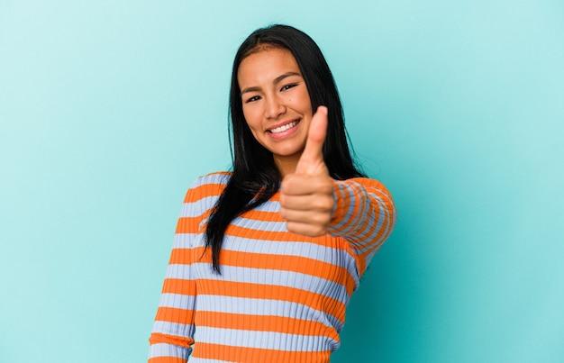 笑顔と親指を上げる青い背景に分離された若いベネズエラの女性