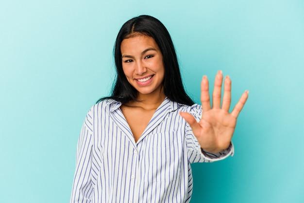 若いベネズエラの女性は、指で5番を示す陽気な笑顔の青い背景で隔離。