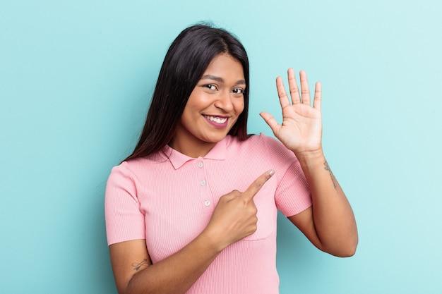 若いベネズエラの女性は、指で5番を示す陽気な笑顔の青い背景に分離されました。