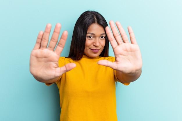 青の背景に孤立した若いベネズエラの女性は、一時停止の標識を示す伸ばした手で立って、あなたを防ぎます。