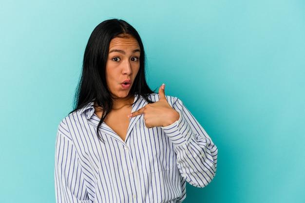 青い背景で隔離された若いベネズエラの女性は、広く笑って、指で指して驚いた。