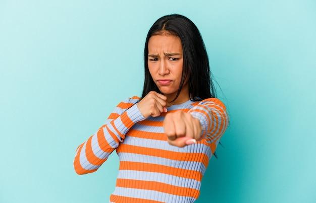 青い背景に孤立した若いベネズエラの女性は、パンチ、怒り、議論のために戦う、ボクシングを投げます。