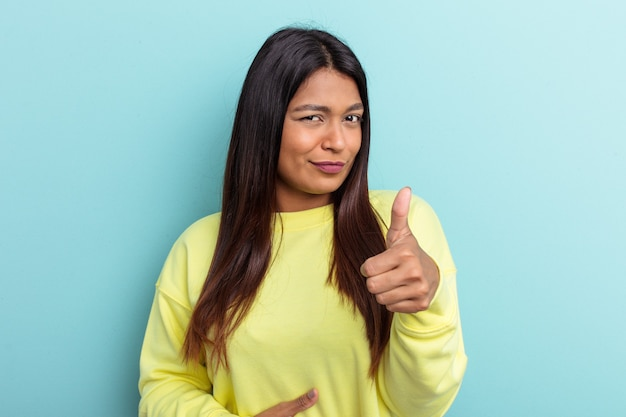 青い背景に分離された若いベネズエラの女性はおなかに触れ、優しく微笑んで、食事と満足の概念。
