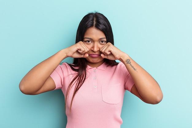 ベネズエラの若い女性は、青い背景で孤独に泣き叫びながら孤立しました。