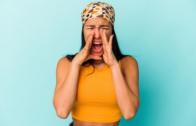 Молодая венесуэльская женщина изолирована на синей стене крича взволнованно.