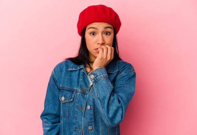 분홍색 배경에 고립된 젊은 베네수엘라 여성은 손톱을 물어뜯고 긴장하고 매우 불안해합니다.