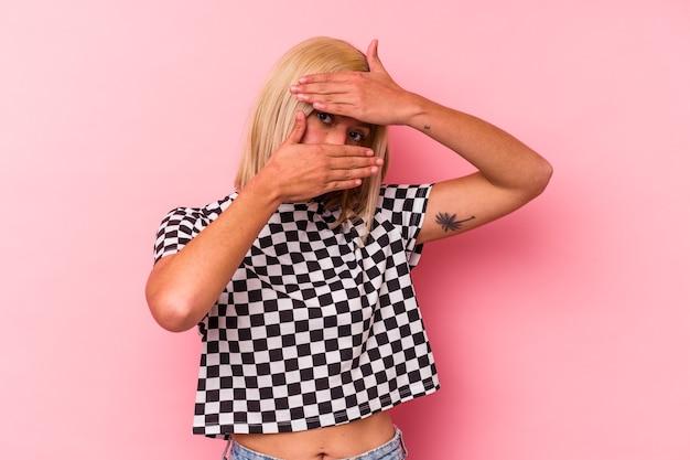 ピンクの背景で隔離された若いベネズエラの女性は、恥ずかしい顔を覆って、指を通してカメラに点滅します。