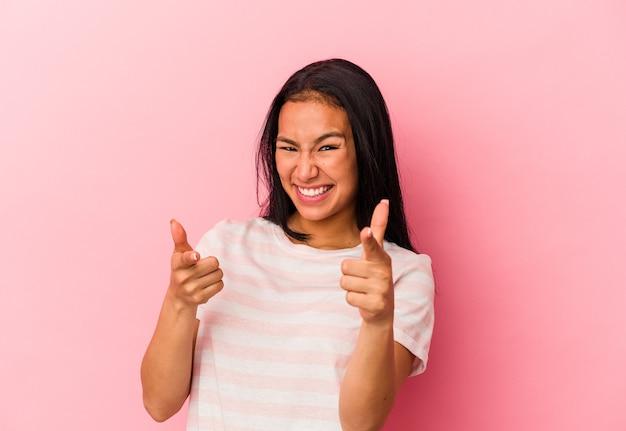 분홍색 배경에 격리된 젊은 베네수엘라 여성이 앞을 가리키며 밝은 미소를 짓고 있습니다.
