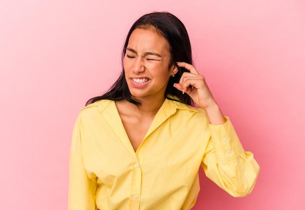 분홍색 배경에 고립된 젊은 베네수엘라 여성은 큰 소리로 스트레스를 받고 절망적으로 귀를 덮고 있습니다.