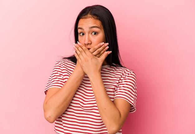 心配そうに見える手で口を覆っているピンクの背景に分離された若いベネズエラの女性。