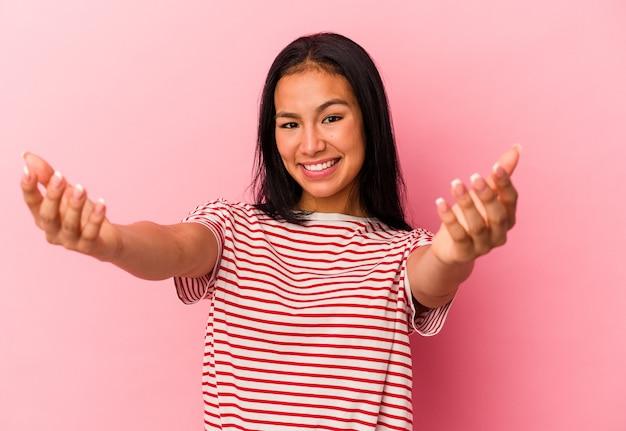 ピンクの背景に分離された若いベネズエラの女性は、カメラに抱擁を与えることに自信を持っています。