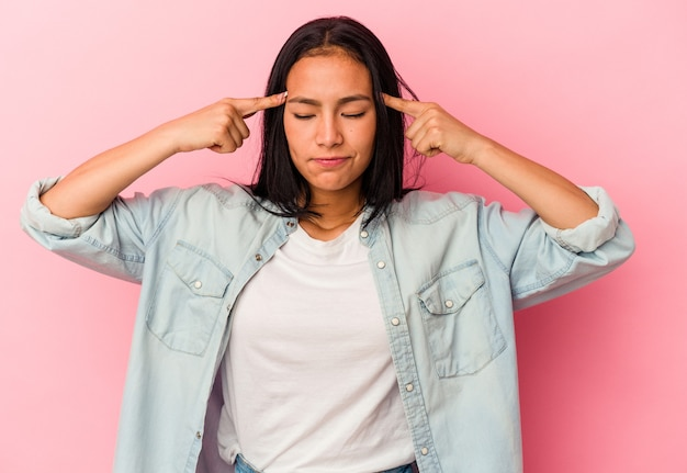 Молодая венесуэльская женщина, изолированная на розовом фоне, сосредоточилась на задаче, держа указательные пальцы, указывая головой.