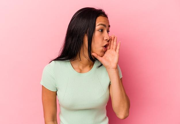 ピンクの背景に分離された若いベネズエラの女性は、秘密のホットブレーキニュースを言って脇を見ています