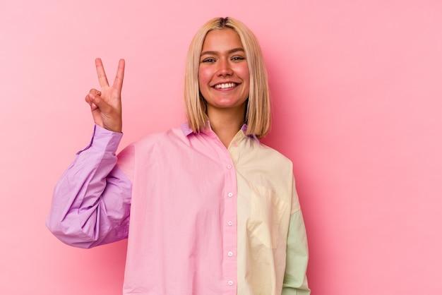 ピンクの背景に分離された若いベネズエラの女性は、指で平和のシンボルを示して楽しくてのんきです。