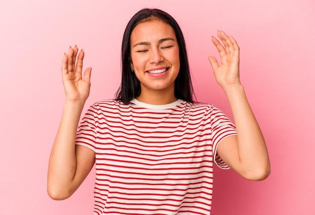 ピンクの背景に孤立した若いベネズエラの女性は、たくさん笑ってうれしそうです。幸福の概念。