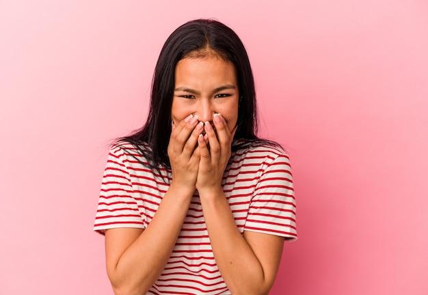ピンクの背景に孤立した若いベネズエラの女性は、手で口を覆って、何かについて笑っています。