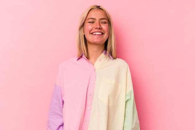 ピンクの背景に分離された若いベネズエラの女性は笑って目を閉じ、リラックスして幸せを感じます。
