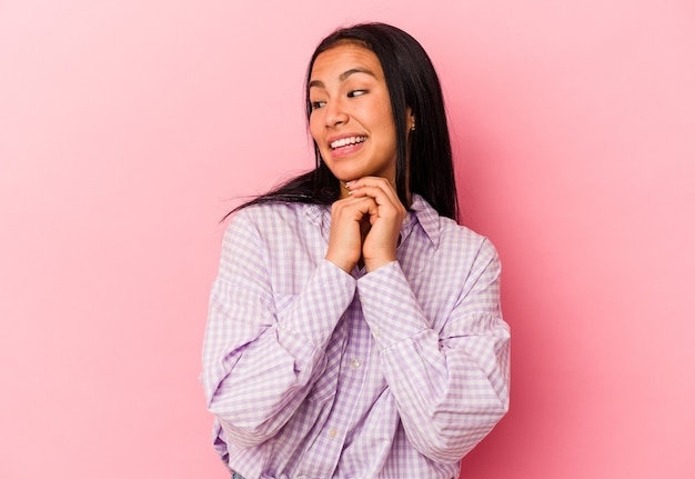Молодая венесуэльская женщина, изолированная на розовом фоне, молясь о удаче, поражена и открыла рот, глядя вперед.