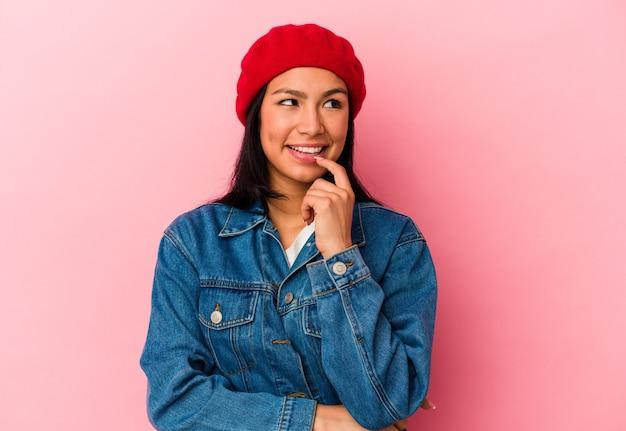 ピンクの背景に分離された若いベネズエラの女性は、コピースペースを見ている何かについて考えてリラックスしました。