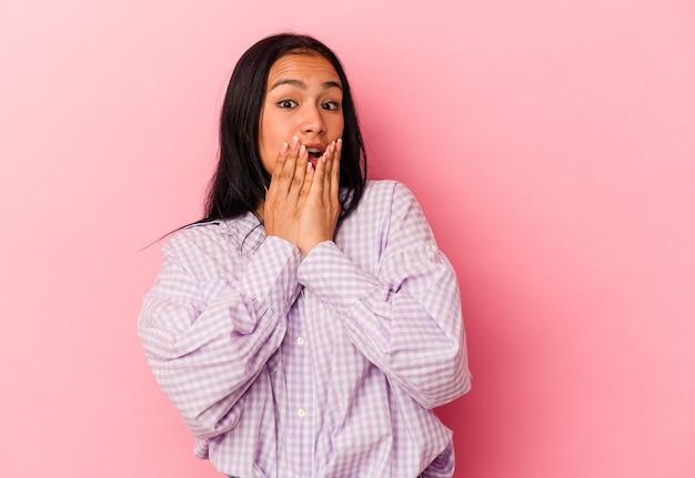 분홍색 배경에 고립된 젊은 베네수엘라 여성은 충격을 받고 손으로 입을 가리고 새로운 것을 발견하기를 열망했습니다.