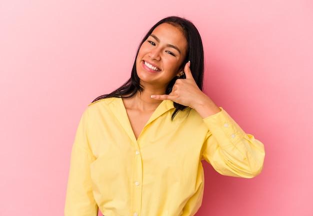 指で携帯電話の呼び出しジェスチャーを示すピンクの背景に分離された若いベネズエラの女性。