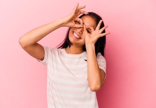 ピンクの背景に分離された若いベネズエラの女性は、目の上に大丈夫サインを示しています