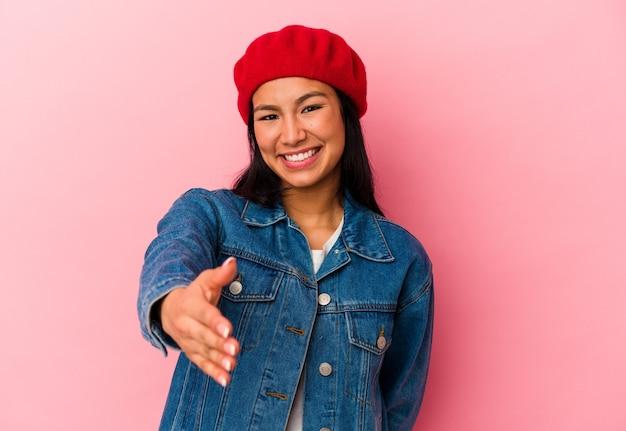 挨拶のジェスチャーでカメラに手を伸ばしてピンクの背景に分離された若いベネズエラの女性。