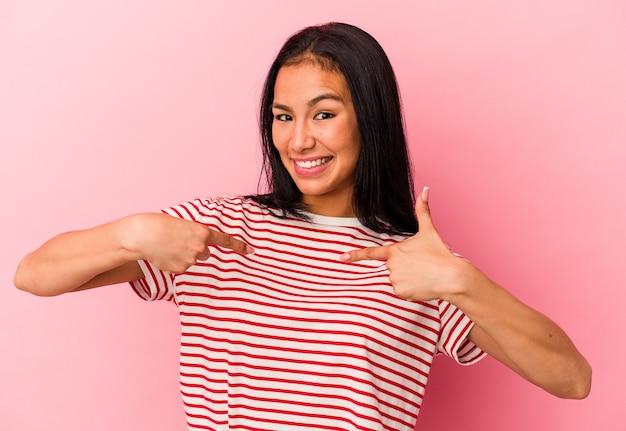 ピンクの背景に分離された若いベネズエラの女性は、広く笑って、指で指して驚いた。