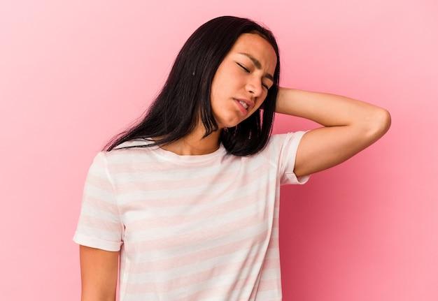 ピンクの背景に孤立した若いベネズエラの女性は疲れていて、頭に手を置いて非常に眠いです。