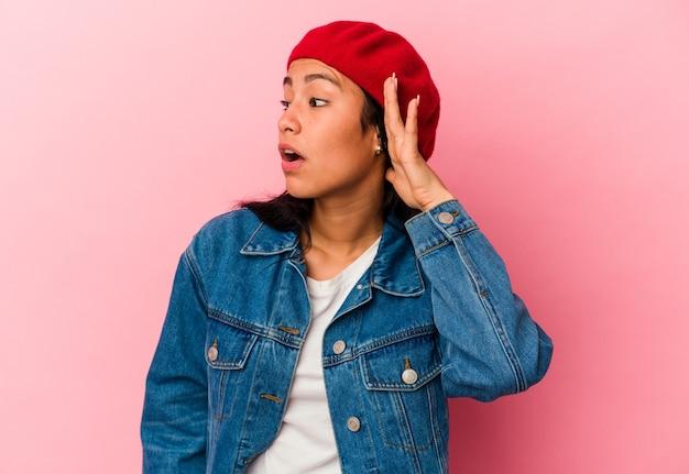 ゴシップを聴こうとしているピンクの背景に分離された若いベネズエラの女性。