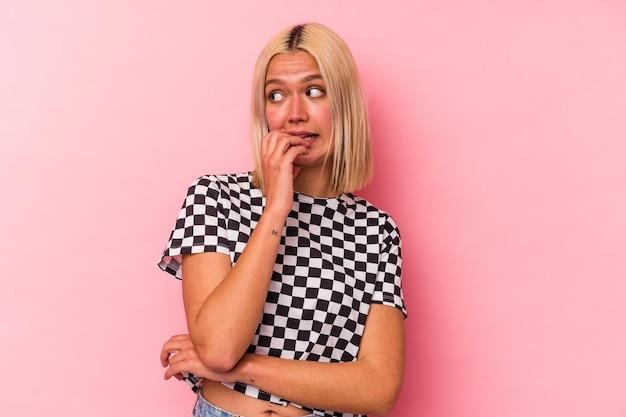 Молодая венесуэльская женщина изолирована на розовой стене, кусая ногти, нервная и очень взволнованная.