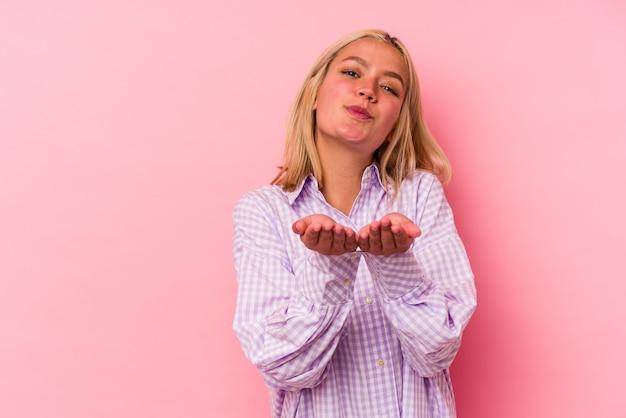 Молодая венесуэльская женщина изолирована на розовой стене, складывая губы и держа ладони, чтобы послать воздушный поцелуй.