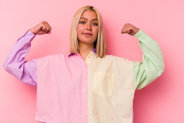 팔, 여성 힘의 상징으로 힘 제스처를 보여주는 분홍색 벽에 고립 된 젊은 베네수엘라 여자 프리미엄 사진
