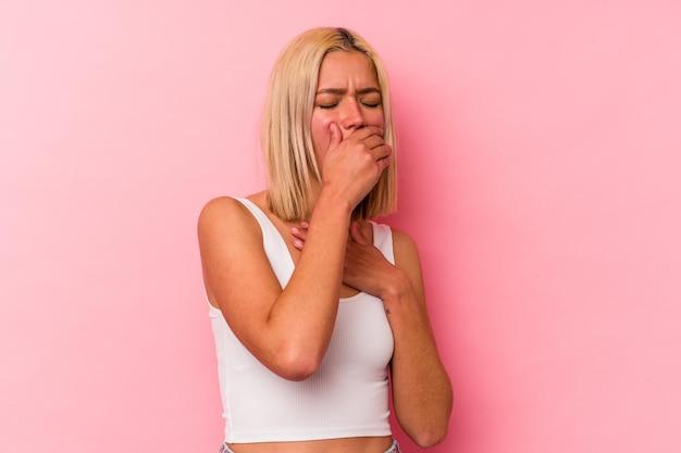 Молодая венесуэльская женщина, изолированная на розовой стене, страдает от боли в горле из-за вируса или инфекции.
