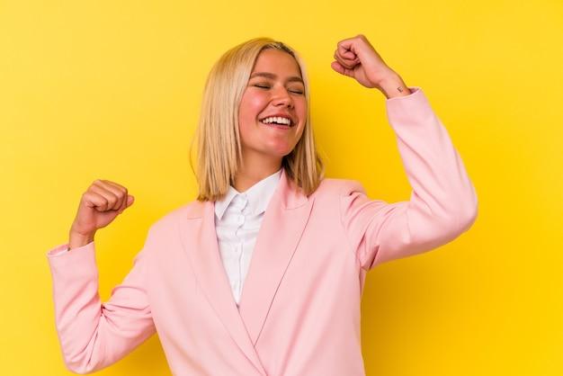 特別な日を祝う黄色の背景に孤立した若いベネズエラの女性は、エネルギーでジャンプして腕を上げます。