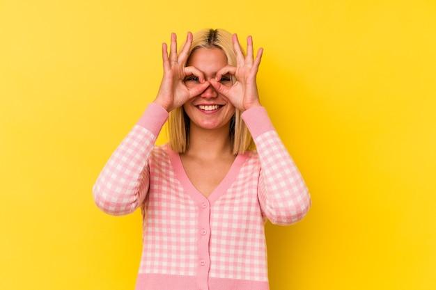 黄色の背景で隔離された若いベネズエラの女性は、目に大丈夫なジェスチャーを維持して興奮しました。