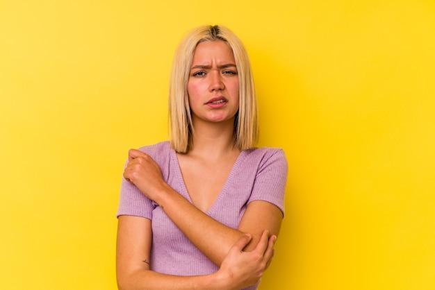 ひじをマッサージし、悪い動きの後に苦しんでいる黄色の背景に分離された若いベネズエラの女性。