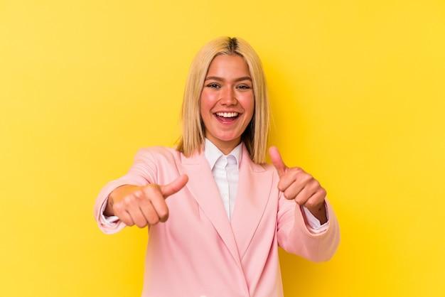 젊은 베네수엘라 여자 두 엄지 손가락, 미소와 자신감을 올리는 노란색 배경에 고립.
