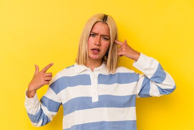人差し指で失望のジェスチャーを示す黄色の背景に分離された若いベネズエラの女性。