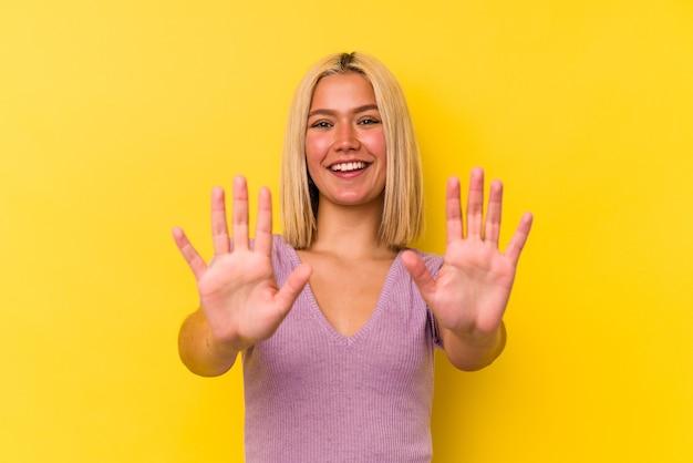 Молодая венесуэльская женщина, изолированные на желтом фоне, показывает номер десять руками.