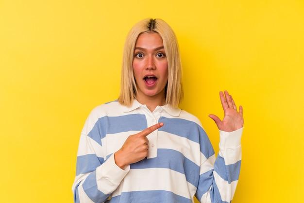 Молодая венесуэльская женщина, изолированных на желтом фоне, улыбается веселый, показывая номер пять с пальцами.