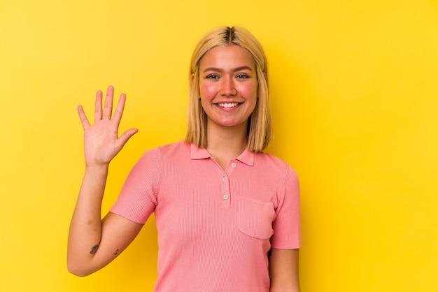 黄色の背景に分離された若いベネズエラの女性は、指で5番を示して陽気に笑っています。
