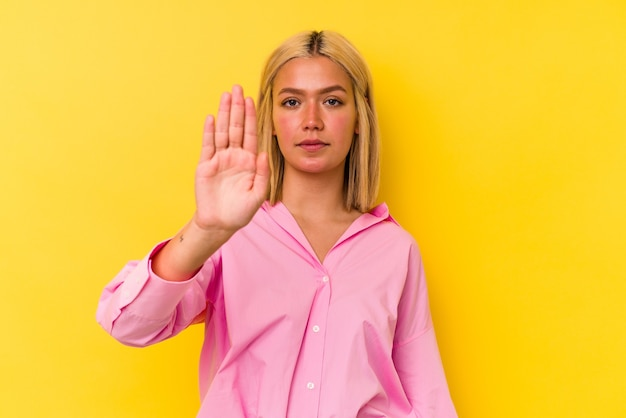黄色の背景に孤立した若いベネズエラの女性は、一時停止の標識を示す伸ばした手で立って、あなたを防ぎます。