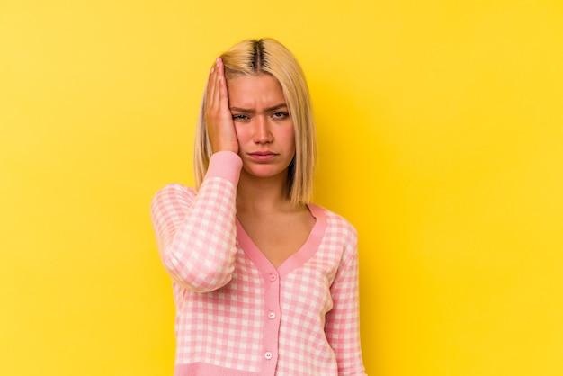 黄色の背景に孤立した若いベネズエラの女性は疲れていて、頭に手を置いて非常に眠いです。
