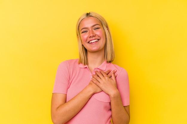 心に手を置いて笑って、幸せの概念、黄色の壁に孤立した若いベネズエラの女性。