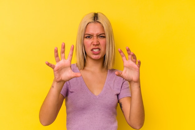 猫を模倣した爪、攻撃的なジェスチャーを示す黄色の壁に隔離された若いベネズエラの女性。