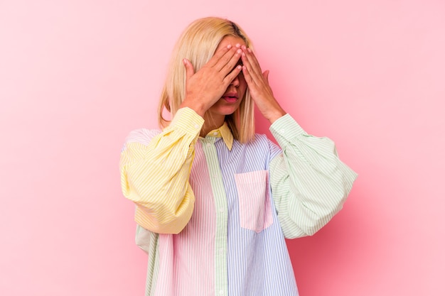 Young venezuelan woman isolated on pink background afraid covering eyes with hands.