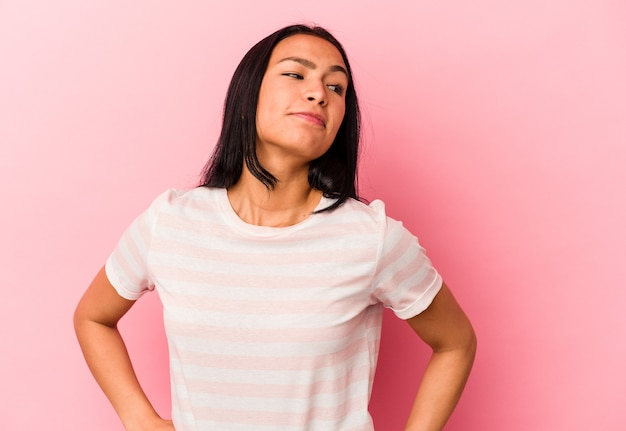 Young venezuelan woman isolated on pink background dreaming of achieving goals and purposes Premium Photo